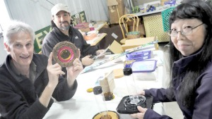 "Last Saturday morning at the New Paltz ReUse Center, John Wackman, Eric Bravo and Alyce Conklin created ""recycling recipes"" for people wondering what to do with odds and ends available at the center. The project ideas have been posted by the materials so others can use them. (photo by Lauren Thomas)"